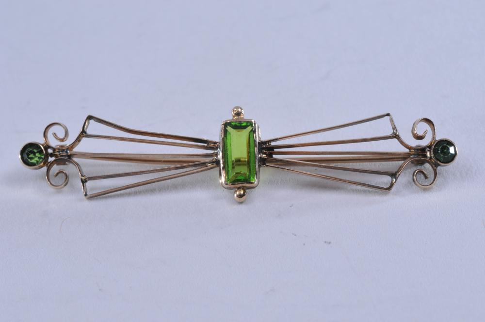 Lot 217: 10k yellow gold brooch, with three peridots. Center stone is rectangular, measuring 8.5 x 5mm. Round stone on each end, 3.5mm each. Overall size of the brooch is 56 x 12mm. Hallmarked 10k. Total weight of 2.6g.