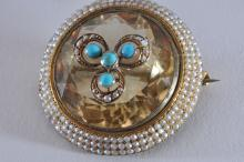 Lot 223: 14k yellow gold brooch. Featuring a large citrine, surrounded by three rows of small seed pearls. Center décor of four turquoise stones and small seed pearls. Overall diameter of 35mm. Round citrine is approximately 26mm in diameter, and is drilled t