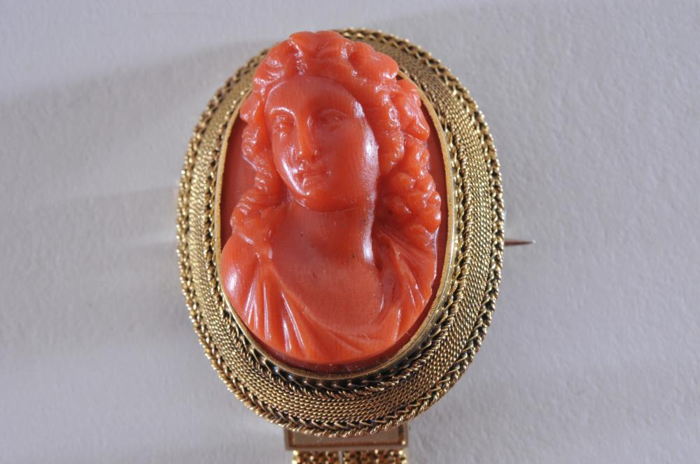 Lot 224: 14k yellow gold brooch. Etruscan style, with coral carving of woman. Elaborate detailing and milgrain work Overall size is 54.5 x 26mm. Coral measures 26 x 19mm. Total weight of 9.4g. No hallmarks, tests as 14k (or slightly higher) gold.