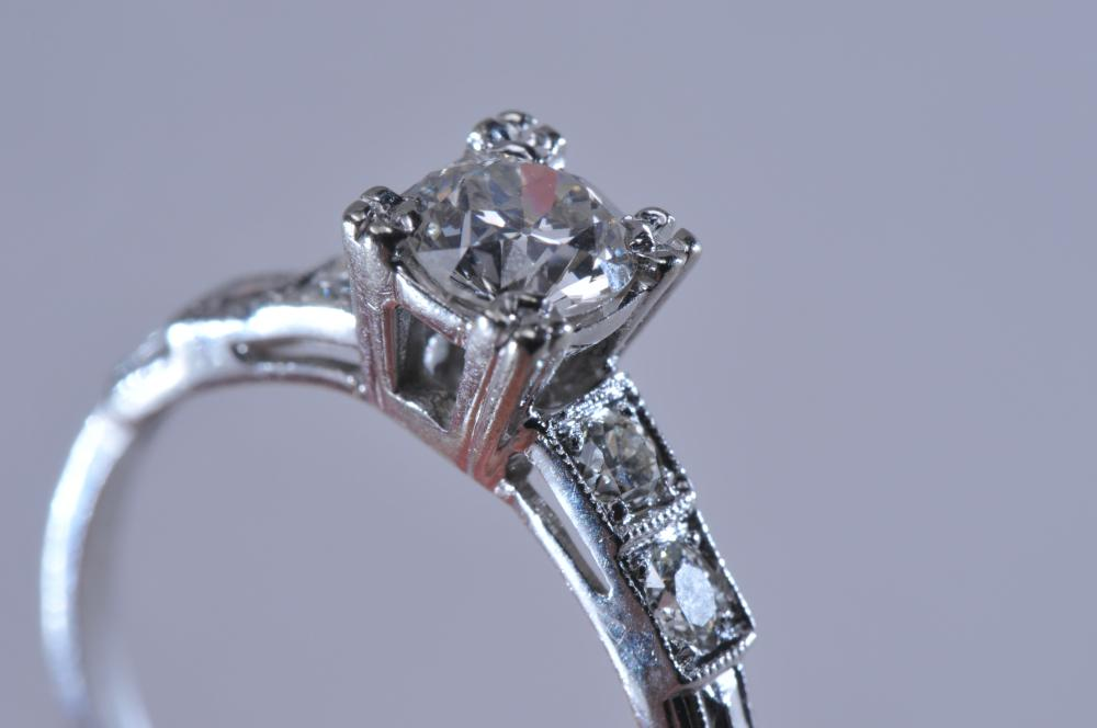 Lot 221: Platinum and diamond ring. Center diamond is a European cut, near colorless, measuring approximately 4.8mm in diameter. Two diamonds on each side, mixed cuts (one single-cut, one transitional, one round brilliant). Finger size 6.5. No hallmarks, tota