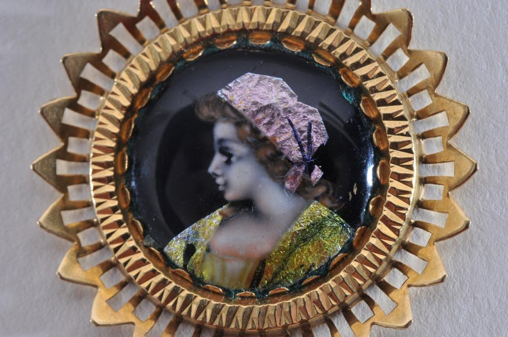 "Lot 226: 18k yellow gold french enamal pendant. Signed 'Email D'Art"". Portrait of a woman on a black background. Overall size is 32mm, enamel pendant is 18.5mm. Hallmarked 750. Total weight of 4.7g."