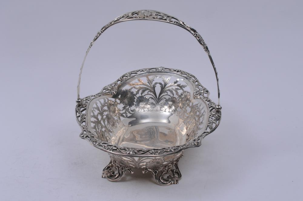 "Lot 231: Large sterling silver pierced decorated footed handled basket. Pierced floral design with pierced leaf scroll feet. RW makers mark. 14"" long. 10-1/2"" wide. 42.1 ozt. Good condition."