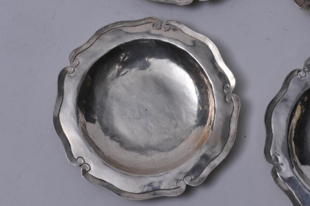 """Lot 244: Four small Arts and Crafts silver butter dishes with decorated rims and hand hammered surface. Unmarked. 4"""" diameter. 4.6 ozt."""