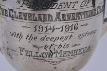 """Lot 252: Sterling silver two handled trophy. """"The Cleveland Advertising Club"""". 1914-1916. Presented to William Ganson Rose. Arts and Crafts. Greek Key border. 8-3/4"""" high. 24.1 ozt. Small crease dent on back body."""