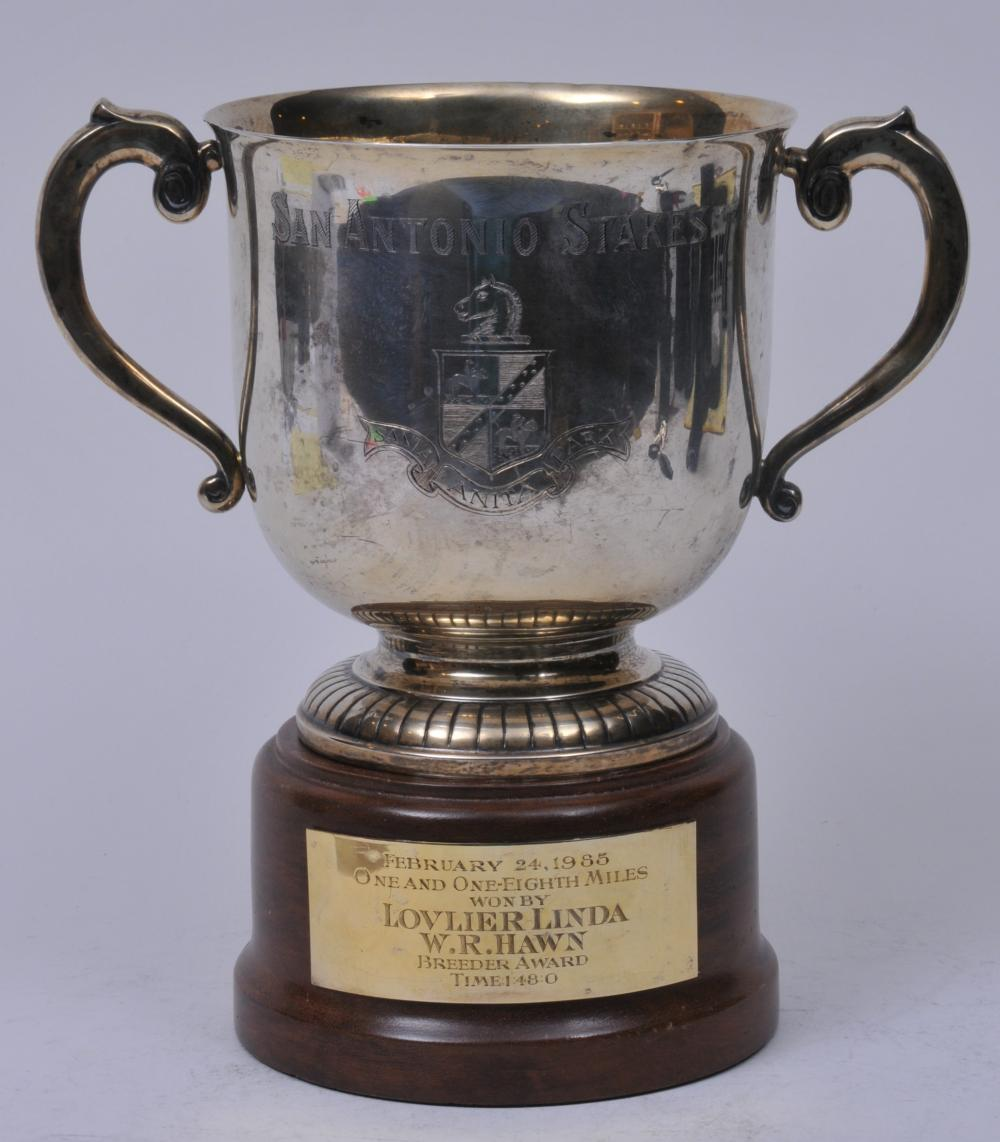"""Lot 259: Sterling silver two handled trophy with reeded base decoration. """"San Antonio Stakes"""". """"Santa Anita Park"""". Wood stand with gilt plaque. Feb. 24, 1985. 1 mile and 1/8 miles. Won by Lovlier Linda. W.R. Hawn Breeder award. Top rim with multiple small den"""