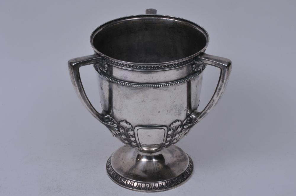 """Lot 255: Gorham sterling silver three-handled trophy. """"The W.B.A."""" Presented to P.E. Werner, 1900. Classical leaf decoration with beaded and geometric border. 8-1/2"""" high. 40.3 ozt. Good condition."""