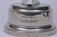 """Lot 266: Metal """"Silver Helmet Rehabilitation Award"""". Presented to Dr. Irving M. Levine. Giver of Hope-Humanitarian Physician Extraordinarius"""". Helmut form with enameled Amvets insignia. 12-3/4"""" high."""