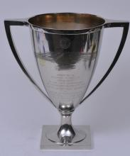 "Lot 274: Large Gorham sterling silver two handled trophy. ""American Optical. Southbridge Mass. Presented to George M. Wells. President of American Optical 1869-1909"". Engraved and raised multiple mill buildings decoration. Raised inscriptions. Gilt interior."