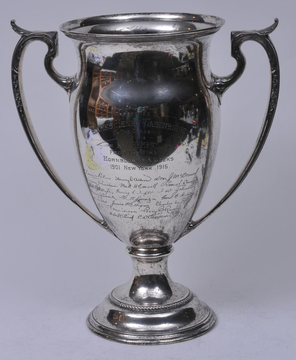 "Lot 275: Reed and Barton large sterling silver two handled trophy. 1916. Presented to James Henry Wainwright. Retirement from Hornblower & Weeks. 15-1/2"" high. 13-1/2"" wide. Rope turned base border. Good condition. 75.5 ozt."