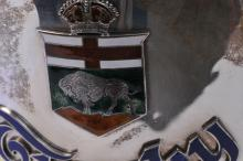 """Lot 278: Impressive large English sterling silver enamel decorated two-handled trophy. """"The Perry Robinson"""" trophy. Presented to The Manitoba Association. Robinson & Co. 1921. Lion mounted handles. Some loss to green enamel badge. Hallmarked on body near hand"""