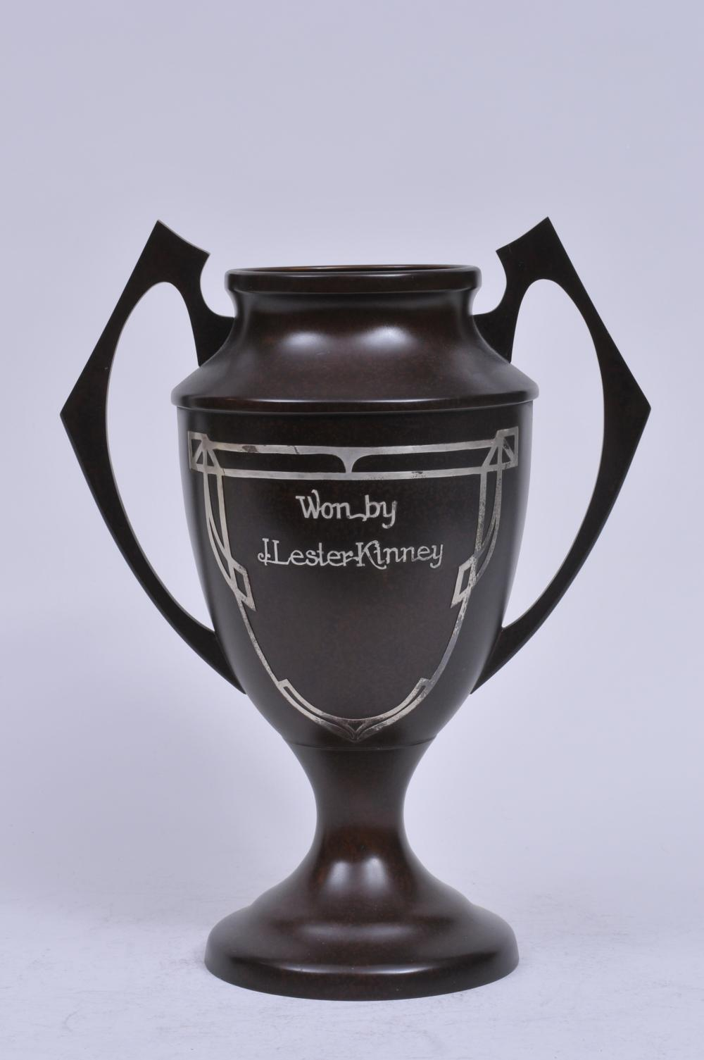 """Lot 289: """"Heinze Art Metal"""" Silver on bronze Arts and Crafts two handled trophy. Good dark patina. """"1927 Goold Bros. Tournament. July 2-3-4th . 1927. Second Flight. Won by J. Lester Kinney"""". Good condition. 14"""" high."""