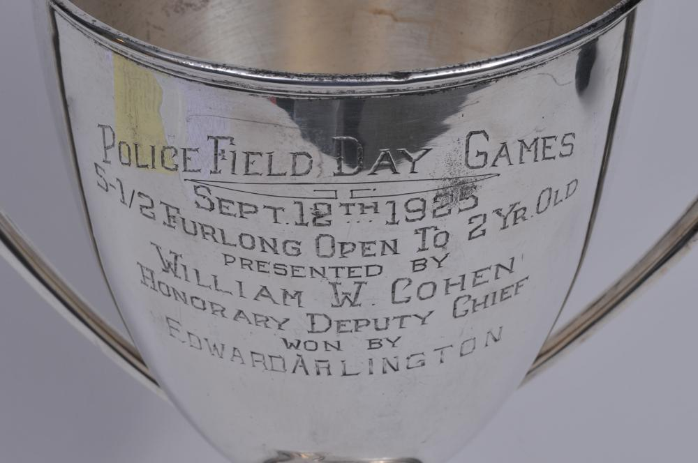 """Lot 283: Large sterling silver two handled horse racing trophy. """"Police Field Day Games. Sept. 12 1925. 5-1/2 Furlong. Open to 2 yr. Old"""". A couple of small dimples on body. Small dents on base rim. 16-1/4"""" high. 12"""" wide. 36.7 ozt."""