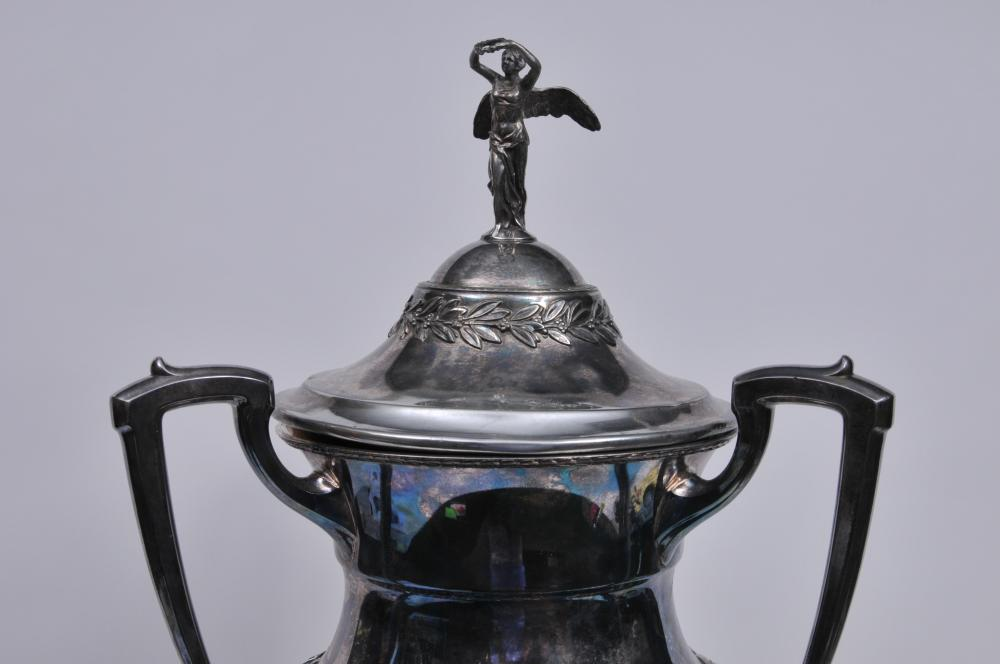 "Lot 284: Large silver-plate three-handled covered trophy. 1928 ""Elks Grand Lodge National Reunion. 1st Prize Patrol Best Drilled. Miami Fla"". Scratches and wear to the silver. 29"" high. Winged Victory figural finial. Cover slightly bent at rim. 35"" high."