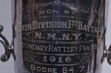 """Lot 280: Reed and Barton silver plate two handled Army trophy. """"Won by Eighth Division. 1st Battalion. N.M.N.Y. Secondary Battery Practice. 1916. Score 84.7"""" Tarnished. Light scratches. 20"""" high."""