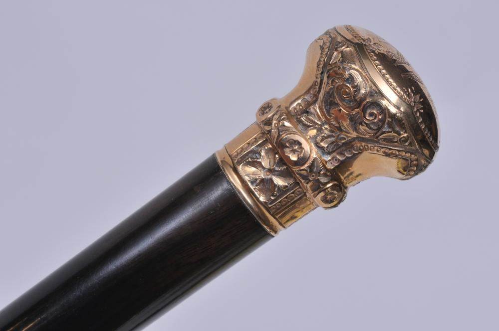 "Lot 285: Wood and gold filled head walking stick. Top engraved with monogram RG. Marked 2, 50A and indecipherable makers mark. Two dings to rim of head. 35-1/2"" long. Head is 1-1/2"" wide. Scuffs and scratches to wood."