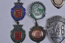 "Lot 340: Lot of nine vintage badges and medals. (1) ""Sheraton 346"" shield. Marked Bastion Brothers (2) Tiffany Metropolitan Life Ins. Co. medal. Sterling silver. (3) State Garden club medal- Sterling silver. (4) ""Waltham Stow"". Auxiliary. Engraved on back- St"