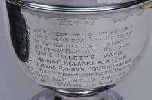 """Lot 293: English sterling silver two handled trophy. """"The East Suffolk Harrier Challenge Cup"""". List of winners. 1927 last winner- Mrs. J.C. Howell's. """"Some Girl"""". 11-1/4"""" high. 12-1/2"""" wide without stand. Good condition. Black wood stand. Hall marked near han"""
