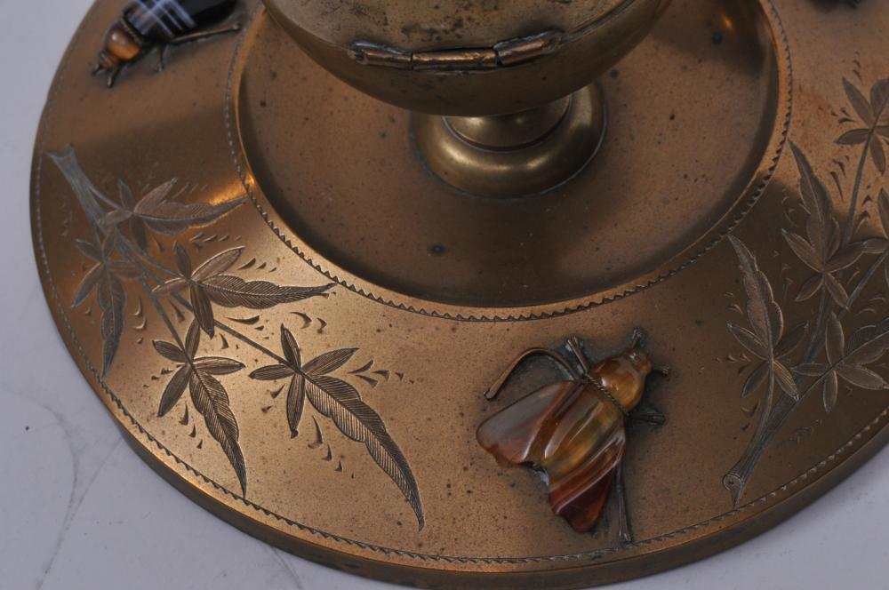"""Lot 300: Late 19th century brass round inkwell. Etched brass floral decoration with carved agate figural mounted insects. Original glass insert. Hinge slightly sprung. 6-1/2"""" diameter."""
