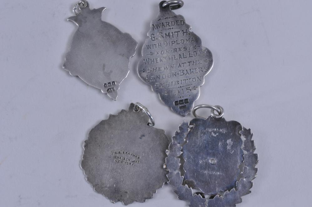 "Lot 308: Lot of four silver medals. (1) Winged foot medal. Marked Sterling. 1-1/2"" diameter. (2) 1915 Reynolds Wheat Meal Bread medal. London. Marked BHJ. 1-3/4"" x 1"". (3) 1896 Evening Telegram Century Run. 1-1/2"" diameter. Marked Braxman. Sterling. (4). Elc"