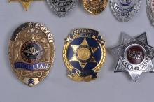 Lot 335: Lot of ten Law Enforcement Badges. (1) Peculiar Police Sergeant (2) Pan Am Security (3) Super Bowl XXXVI (4) Trump Plaza Hotel & Casino Security (5) K-Mart Security (6) Presidential Joint Staff Security (7) Boy Scouts Security (8) Macy's Security (9