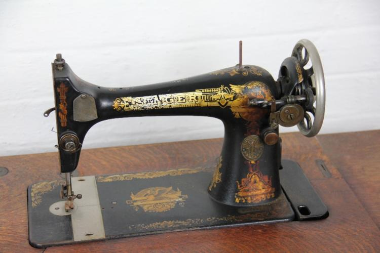 An oak cased Singer treadle sewing machine, with gilt