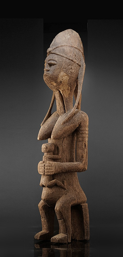 A Bamana maternity, seated on a one leg stool