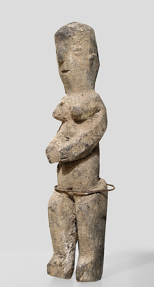 A female Lobi sculpture with an iron ring around the hips