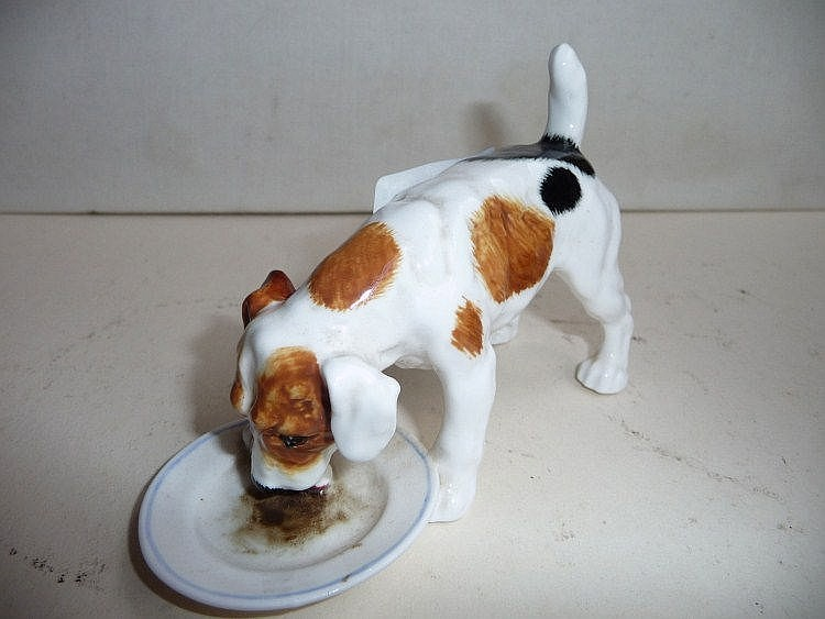 A Royal Doulton figurine of a terrier eating off a