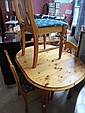 An extending pine kitchen table and three chairs