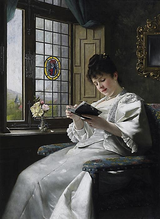 Young woman reading by the window in a white satin dress and gazing into the chateau park.