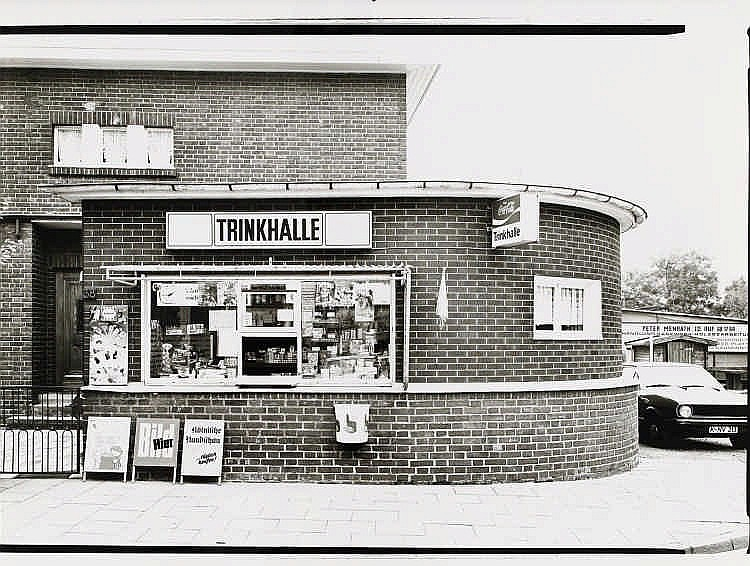 RONKHOLZ, TATA 1940 Krefeld - 1997 Köln Trinkhalle. Strundener Str. 38, Köln-Dellbrück. 1982. Vintage. Gelatinesilberabzug auf Agfa-Papier. 22 x 30,8cm (24 x 31cm). Archivnummer mit Bleistift verso: Nr. 345. - Fotografie minimal gewellt. Ansonsten