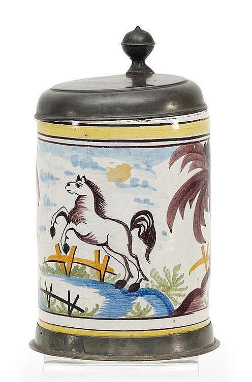 Großer Walzenkrug mit springendem Pferd in Landschaft.       Hannoversch-Münden.     Um 1800.       Beiger Scherben mit weißer Glasur und farbigem Dekor. Zinnmontierung. Höhe 24,5cm. Zustand C.   Blaue Marke.