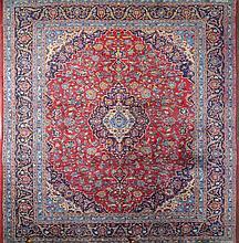 Grand tapis Tebriz (?) à médaillon au décor floral sur fond bleu et rouge.
