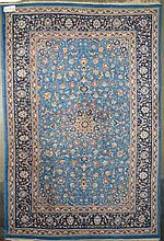 Tapis Naïn (?) au décor floral sur fond bleu et vieux rose. Dim.:308x204cm.