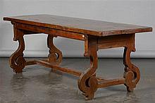 Grande table rectangulaire en noyer. Pieds galbés reliés par une entretoise