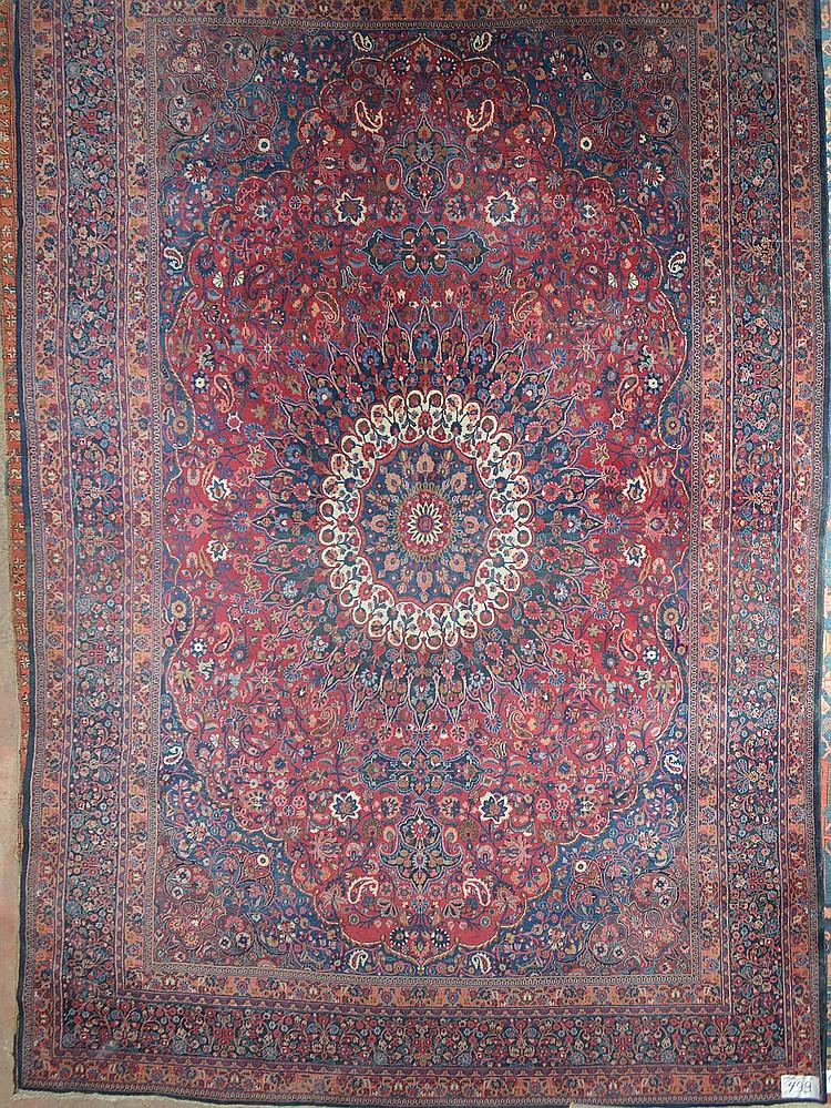 Grand tapis Khorassan fait main en laine à médaillon central et à décor floral rouge, bleu et blanc sur fond rouge et bleu. Signé. Travail iranien. Réduction de chaîne:6fils/cm. Dim.:445,5x315cm.