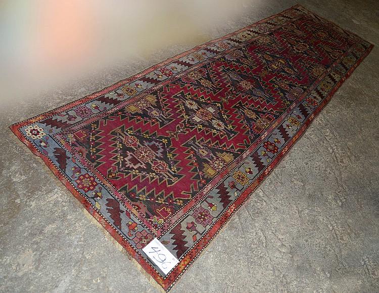 Tapis de couloir Shirvan fait main en laine au décor en médaillons géométrisés noir, rose et beige sur fond magenta. Travail du Caucase. Réduction de chaîne:4fils/cm. Dim.:373x145cm.
