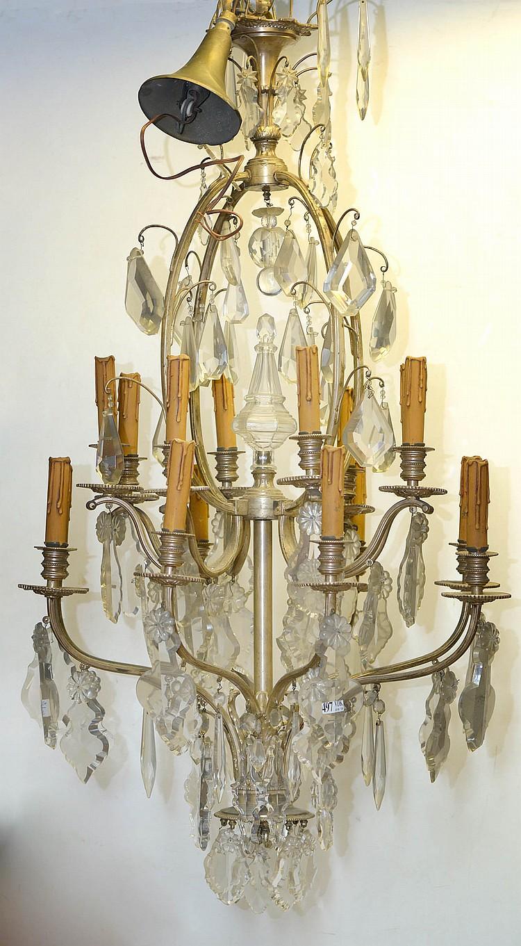 Lustre en bronze argenté muni de pampilles en cristal incolore à seize bras de lumière reparti sur deux étages. Epoque:XXème. (Un manque). H.:+/-100cm.