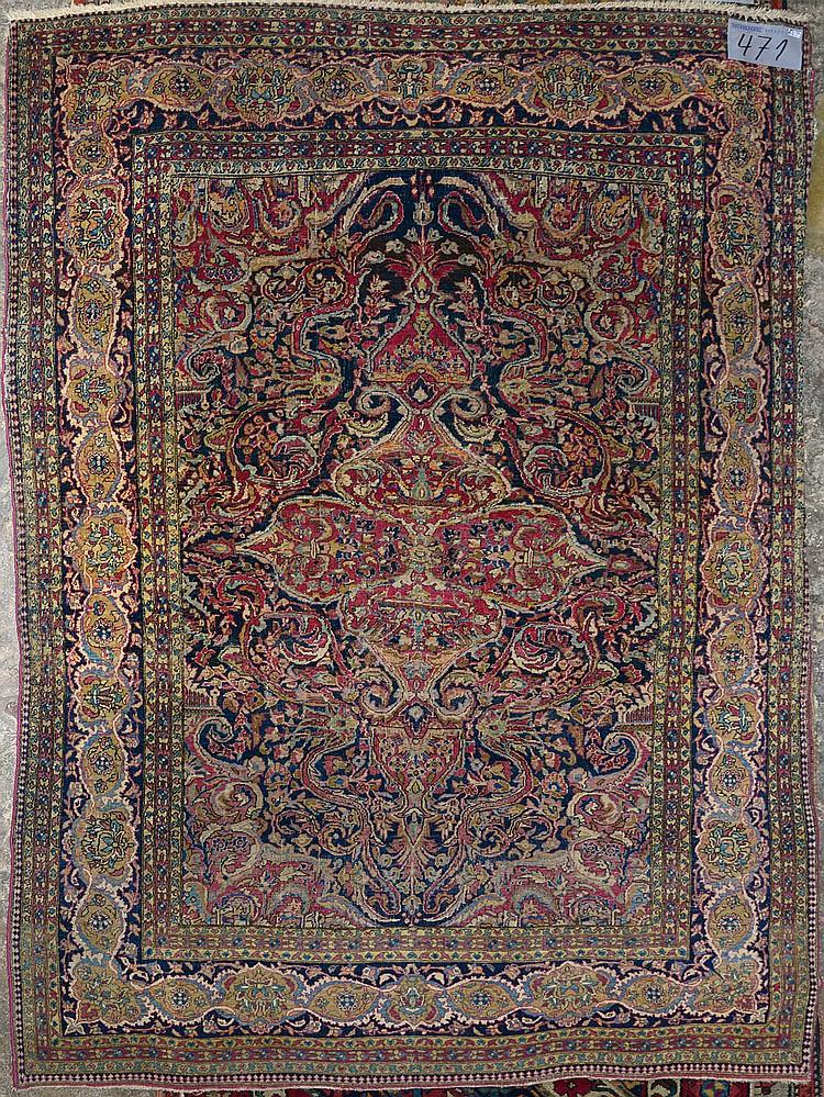 Carpette Ispahan faite main en laine et soie à décor floral et médaillon central rose sur fond bleu, rose, vert et beige. Travail iranien. Epoque: vers 1900. Réduction de chaîne:7fils/cm. (Usures). Dim.:206x141cm.