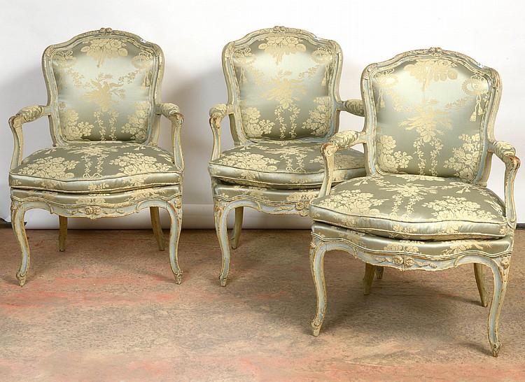 Suite de trois fauteuils cabriolets de style Louis XV en bois rechampi garnis de soie bleue à décor de