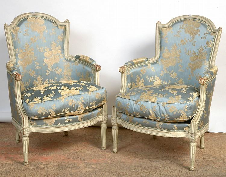 Paire de bergères cabriolet de style Louis XVI en bois sculpté rechampi et garnies de tissu en soie bleue au décor floral de couleur crème. Travail français. Epoque: XVIIIème.