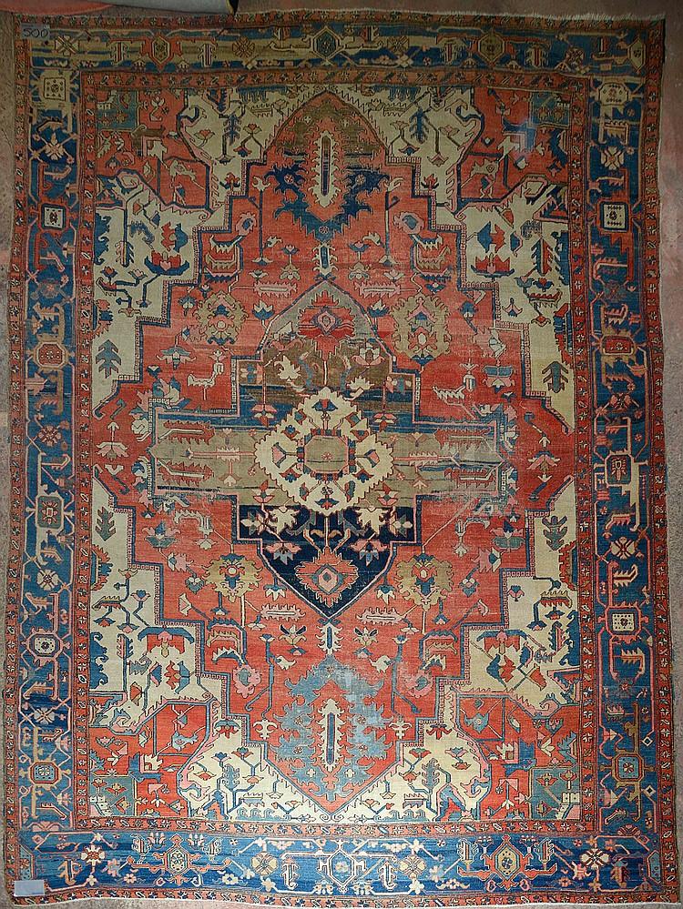 Grand tapis Hériz ancien en laine à médaillon à décor floral géométrisé sur fond beige et bleu. Epoque: vers 1900. (Usures). Dim.:450x329cm.
