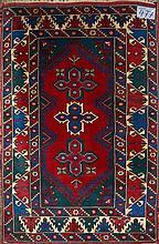 Carpette ancienne faite main en laine décorée de trois médaillons géométriques bleus et rouges sur fond rouge, vert et bleu. Travail turque. Réduction de chaîne:3fils/cm. Dim.:178x117cm.