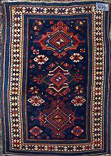 Carpette Shirvan ancienne en laine faite main munie de trois médaillons géométriques et d'un décor floral stylisé vert, rose et bleu sur fond bleu et beige. Travail du Caucase. Réduction de chaîne:4fils/cm. Dim.:173x114cm.