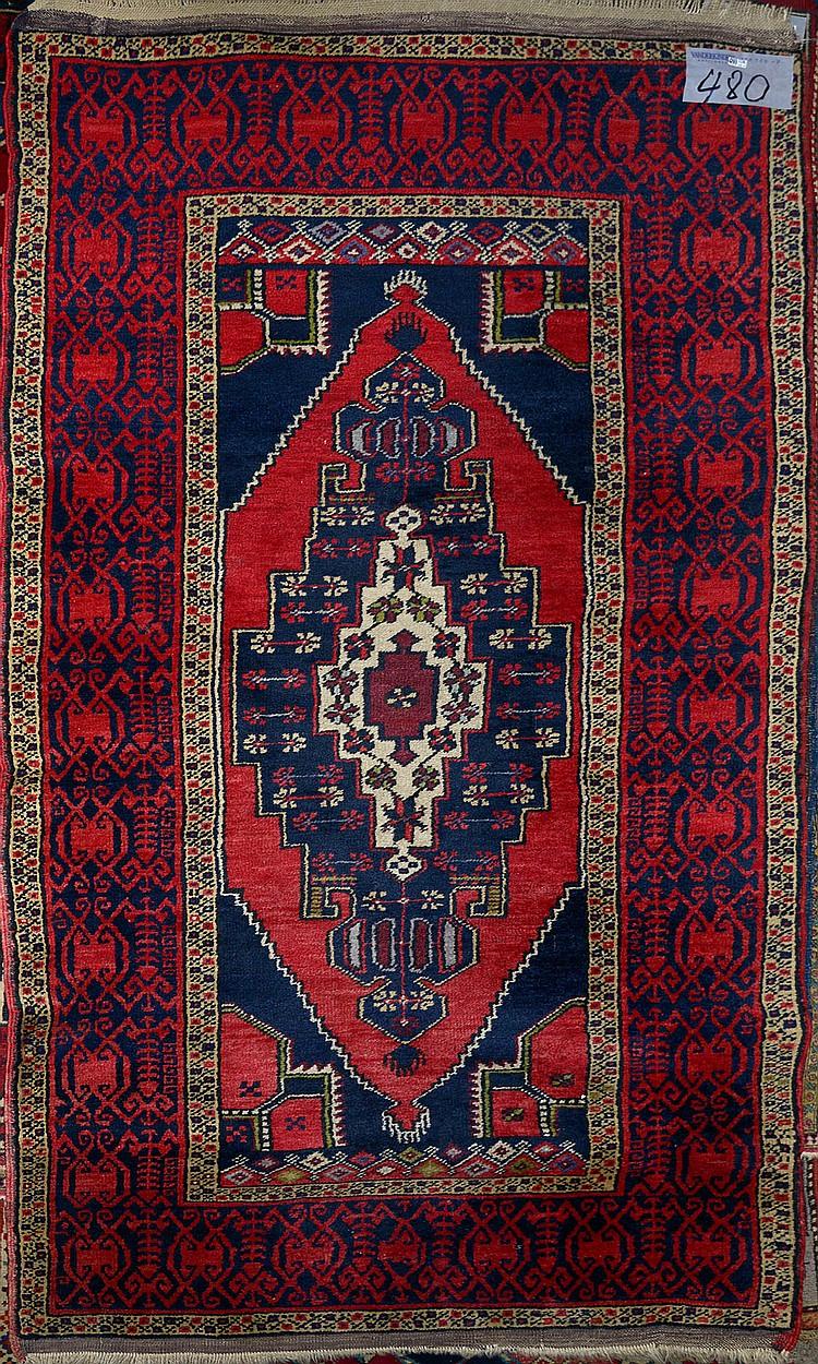 Carpette Shirvan faite main en laine décorée d'un médaillon géométrique central bleu et rouge sur fond bleu dans un rectangle entouré d'une bordure bleue et rouge. Travail du Caucase. Réduction de chaîne:4fils/cm. Dim.:196x103cm.