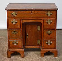 Petit bureau en acajou muni d'un tiroir en ceinture et de deux rangées de trois petits tiroirs entourant une porte centrale. Poignées en bronze doré. Travail anglais. Epoque: XVIIIème. Dim.:78,5x77,5x49cm.