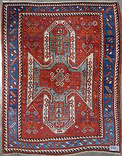 Carpette Kazak faite main en laine décorée d'une croix stylisée beige, bleue et rouge sur fond rouge, bleu foncé et beige. Travail du Caucase. Réduction de chaîne: 6fils/cm. Dim.:260x209cm.