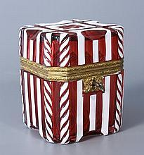 COFFRET à section carrée en verre rose doublé d'émail blanc taillé à bandeaux dont huit à côtes torses, et motif central en étoile. Monture et entrée de serrure en pomponne estampé doré. Haut.