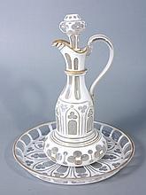AIGUIERE à bouchon et son présentoir en verre doublé d'émail blanc taillé à motifs gothiques à filets dorés. Haut. Totale