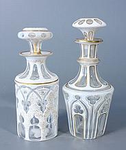 Deux FLACONS et leurs bouchons en verre doublé d'émail blanc taillé de motifs gothiques à filets dorés pour l'un et de motifs orientaux à résille dorée pour l'autre. Haut.